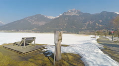 Stone bench at national park in Austrian Alps, snow melting, sunny spring day Stock Footage