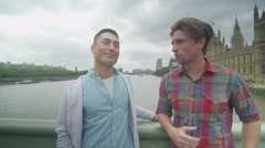 4K Portrait of smiling male friends standing by the side of London River Thames Stock Footage