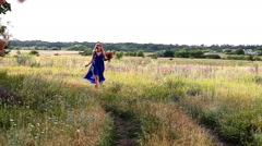 Romantic girl walking on the road in a blue dress Stock Footage