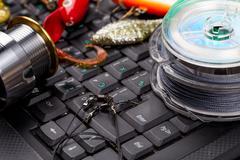 fishing tackles, line, lure, swimbait on keyboard - stock photo