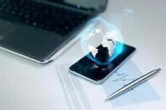 Stock Photo of close up of smartphone with earth globe hologram
