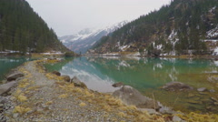 Stony lakeside, forest and mountains reflection in water, electric power lines Stock Footage