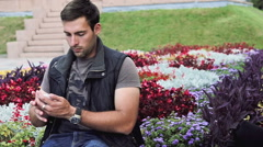 Smart sexy brunette Italian man sitting in the park Stock Footage