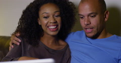 An attractive African American couple watching a movie on a laptop computer. Arkistovideo