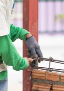 Workers using steel wire and pincers rebar before concrete is poured - stock photo
