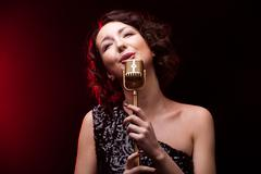 Beautiful girl singer singing lyric song with retro microphone Stock Photos