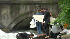 Surfers waiting on the riverside in the English Garden of Munich Stock Footage