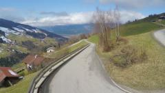 Serpentine road in high mountains, cloudy sky over green slopes, Alpine village Stock Footage