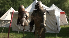 Knight's armor at medieval pageant event white tents Stock Footage