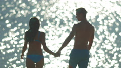 5 in 1 video! Pair walk on beach and hug by bright sunlight reflection on water  Stock Footage