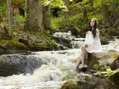 Beautiful brunette on a river - stock photo