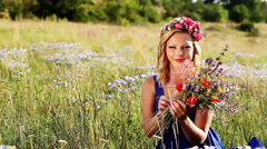 beautiful young girl collects bouquet of wildflowers - stock footage