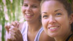 Two women enjoying friendship drinking ice coffee under a tree next to lake Stock Footage