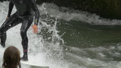 Close up view of a man with black swimsuit surfing on Isar River, Munich - stock footage