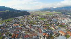 Aerial panorama of Swarovski factory hometown, majestic mountain range around Stock Footage