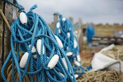 Close up of a tangle of blue fisherman's rope with white floats. - stock photo