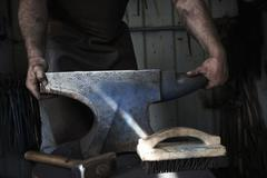 Blacksmith standing at an anvil in a traditional forge. Kuvituskuvat