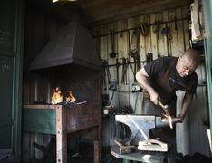 Blacksmith shaping a hot piece of iron on an anvil in a traditional forge with Kuvituskuvat