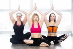 Group of three yogi females sitting in Easy Pose - stock photo