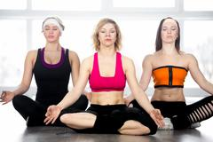 Group of three females meditating in class Stock Photos
