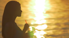 The woman silhouette with cocktail, drink and dream on the beach by the bright - stock footage