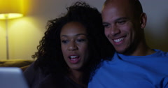 An attractive African American couple watching a movie on a laptop computer. Stock Footage