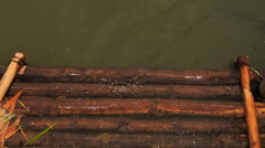 Transparent river water washes out wooden logs of bank platform Stock Footage