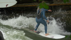 Woman surfing on Isar River in Munich - stock footage