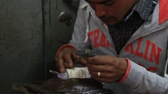 Tibetan master making souvenirs from metal. Leh, Ladakh, India Stock Footage