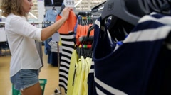Young Shopaholic Woman Choosing Dress in Fashion Store Stock Footage