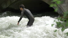 Two men surfing on Isar River's water in Munich - stock footage