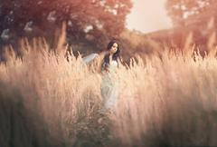 Beautiful, romantic woman in fairytale, wood nymph among tall grass and rays of Stock Photos
