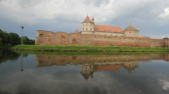 Beautiful castle and fortress reflecting on tranquil lake water, spring Stock Footage