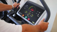 Hands of man training on stationary bike and display with text Stock Footage