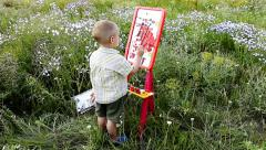 little boy paints on an easel outdoors - stock footage