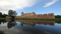 Beautiful fortress in nature landscape, stronghold reflecting in lake water - stock footage