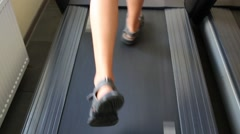 Legs of boy teen training on treadmill in fitness center Stock Footage