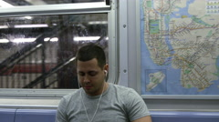 Man listening to music on earbuds riding subway train pulling into station 4K NY Stock Footage