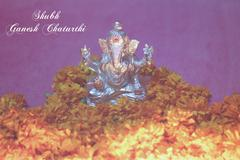 Stock Photo of Ganesh idol with sunflower and oil lamp
