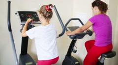 Daughter and mother training on exercisers in fitness center Stock Footage
