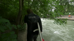 Walking with a surfboard on the riverside in Munich Stock Footage
