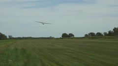 Glider landing on a grass runway Stock Footage