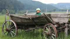 Single baby boy in wooden cart, countryside holiday Stock Footage