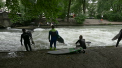 Surfers on the riverside in the English Garden, Munich Stock Footage