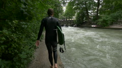 Surfer walking on the riverside in Munich Stock Footage