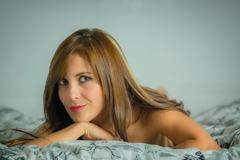 Beautiful young sexy latin woman lying in bed Stock Photos