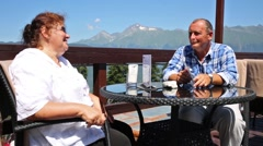 Elderly pair sit in open air restaurant among mountains at summer Stock Footage