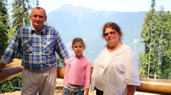 Girl, grandmother, grandfather look at beautiful mountains Stock Footage