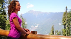 Pretty woman smiles and looks at beautiful mountains Arkistovideo