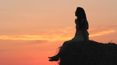 Beautiful woman silhouette sitting on straw ball admire nature at sunset Stock Footage